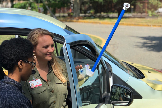 Photo of two women standing in front of a car that has a heat sensor clipped to its passenger door window