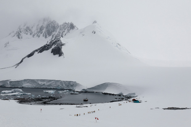 tourists walkinng along a ice-free inlet with towering snowbanks on the surrounding terrain