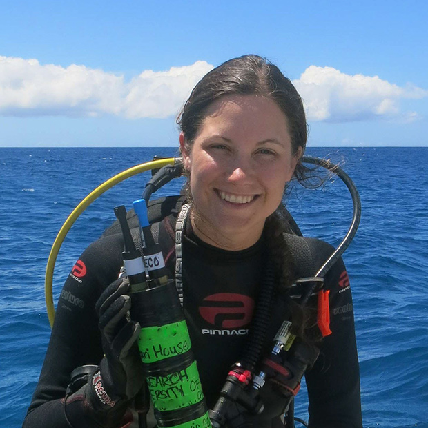 Danielle Claar in scuba gear, sitting on a boat with the ocean and sky behind her