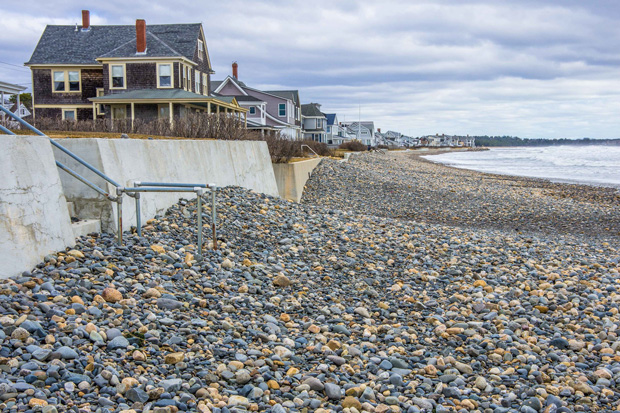 A lon line of beach houses perch above a sea wall. Below, the beach is completely denuded of sand, instead covered by small rocks.