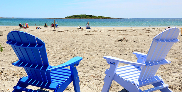 Two empty beach chairs looking out over a wide sandy beach, with an offshore, tree-covered island
