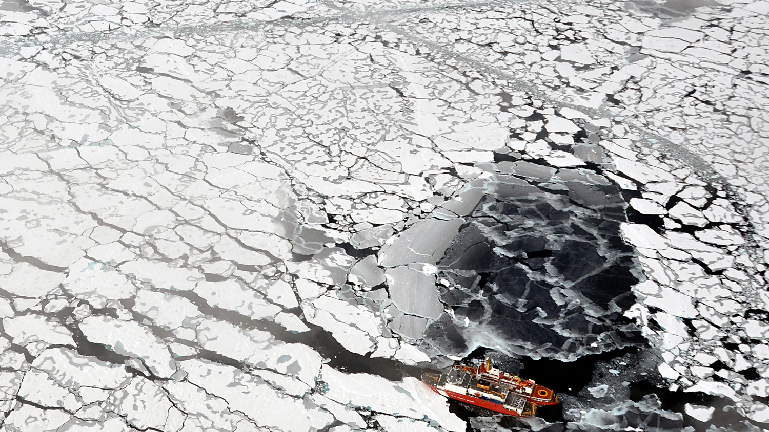 Aerial photo of U.S. Coast Guard icebreaker Healy surrounding by ice floes