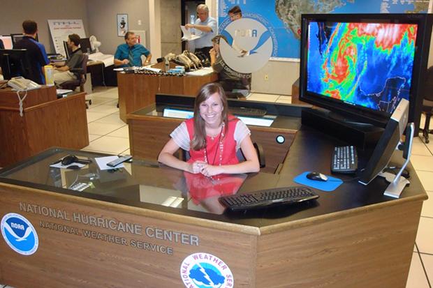 Sarah Larson sitting at desk at the National Hurricane Center