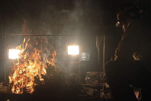 A fire expert ignites and monitors a test burn