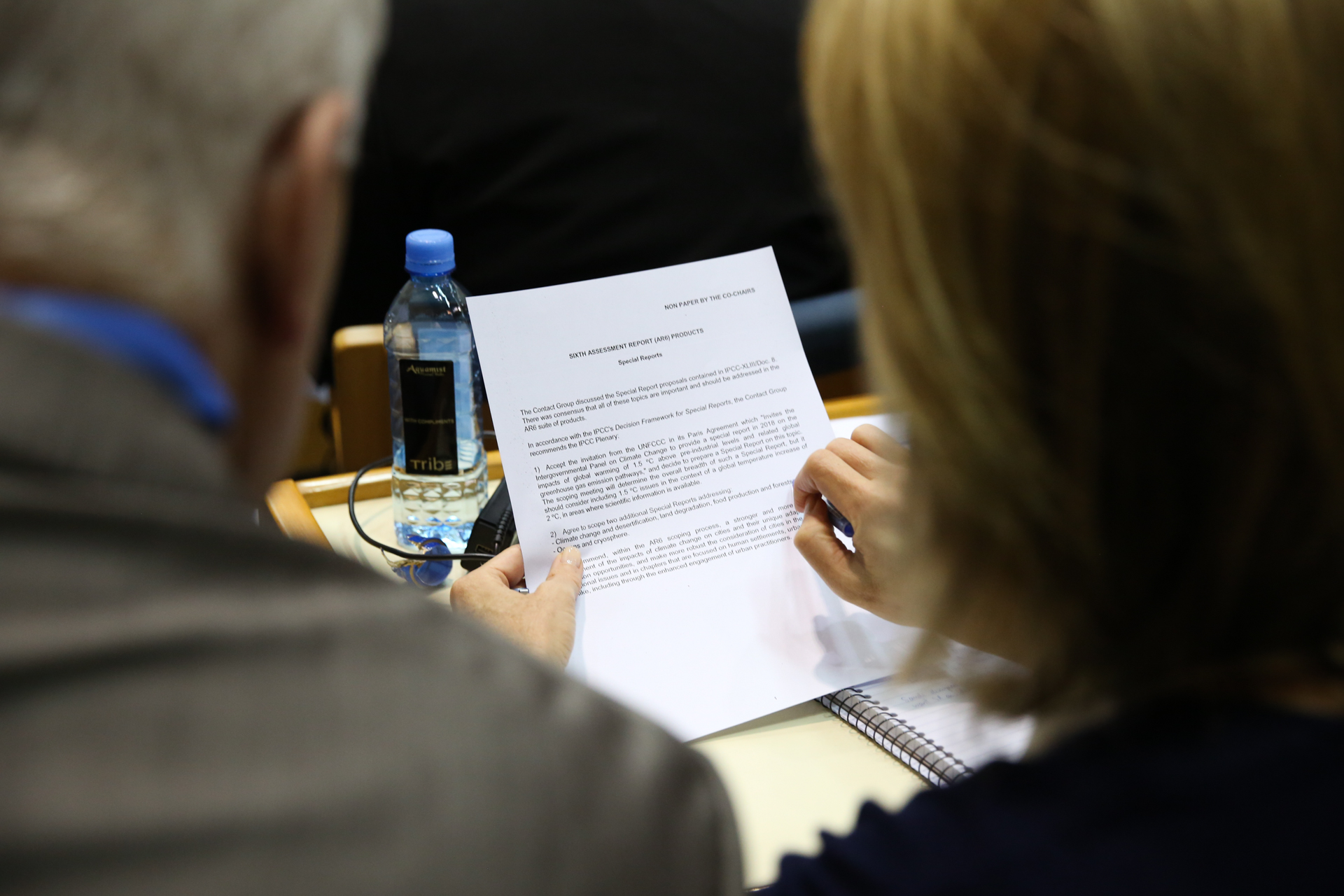 A photo looking over the shoulders of two delegates as they review text