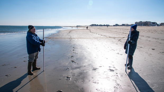 Dressed for winter weather, two volunteers stand on a beach in the surf zone at low tide. They each hold a measuring pole connected by ~10 feet of rope.