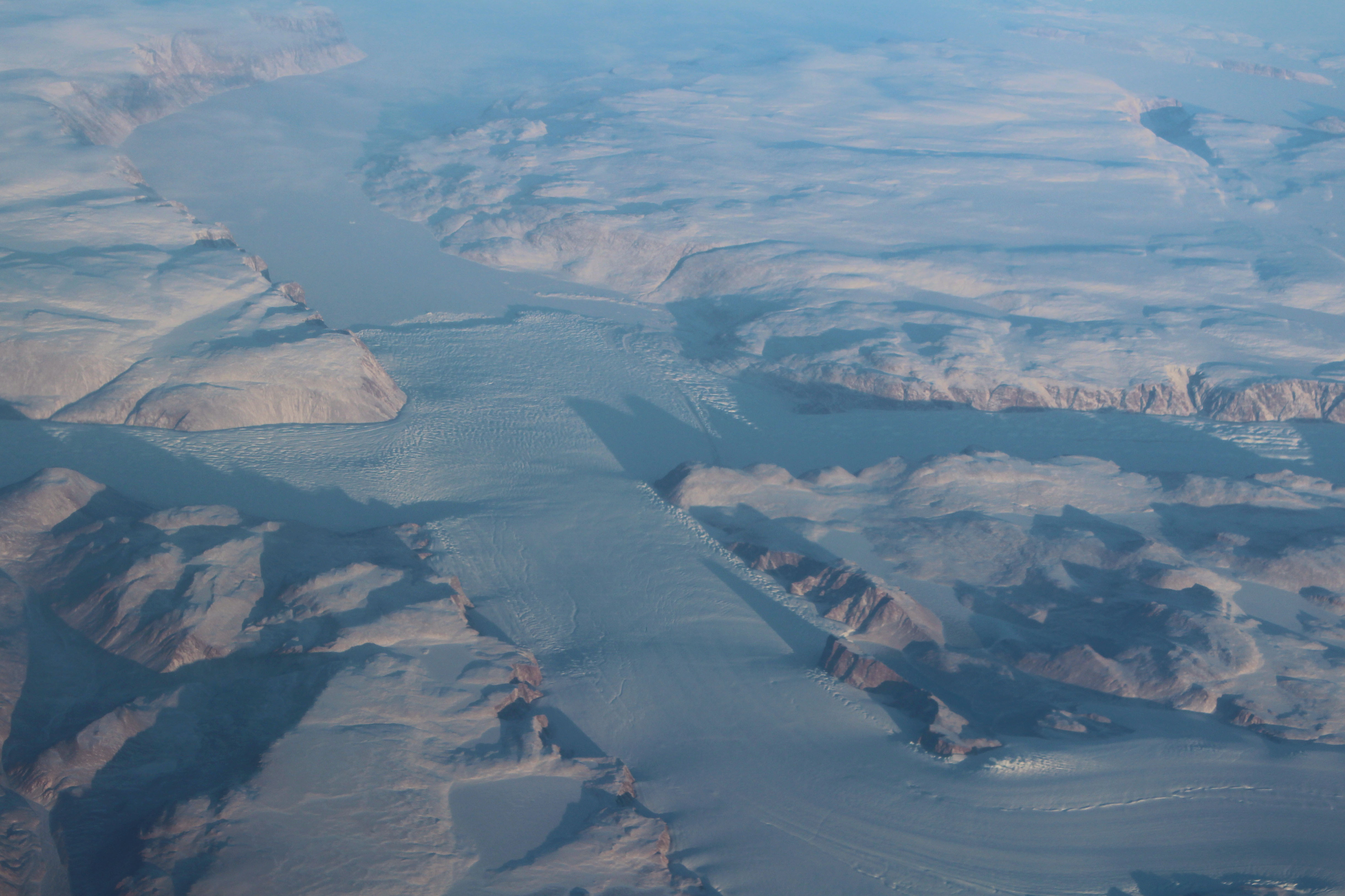 aircraft photo of a greenland glacier emptying into a frozen fjord