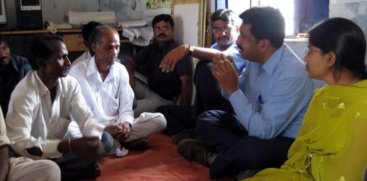 Photo of researcher conversing with farmers
