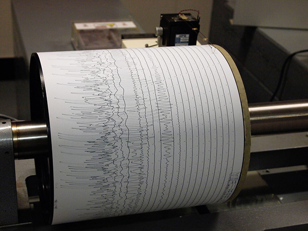 a photograph of a paper-covered drum of a seismograph with the squiggly lines that trace seismic activity