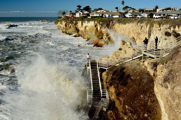 photo of pounding surf submerging a beach below a bluff lined with houses