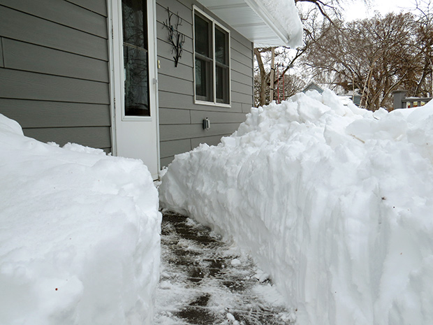 Photo of a cleared sidewalk lined by a tunnel of snow several feet deep leading to the door of a house in South Dakota
