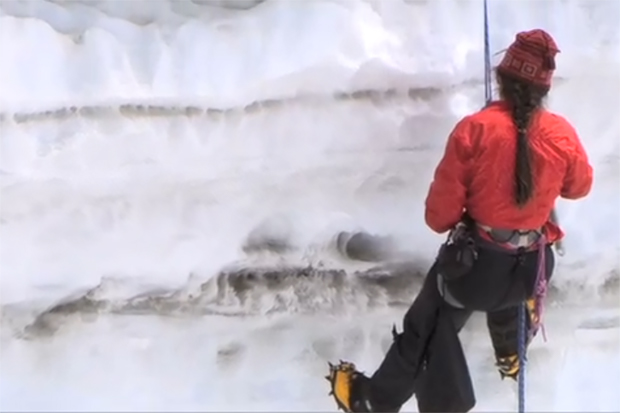 Scientist in a climbing harness descends into a snow pit that shows different layers of soot mixed with snow