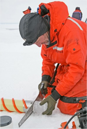 photo of man sawing into an ice core in the field
