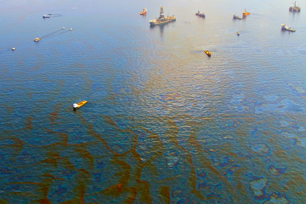 Aerial view of multiple small vessels skimming oil in booms amid a large oil slick in the GUlf of Mexico during the Deepwater Horizon disaster in 2010