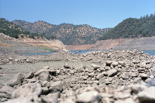 a photo of the rock-strewn bottom of Don Pedro Reservoir, exposed due to drought