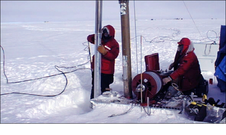 Photo of researchers drilling into snow