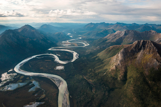 Aerial photo of a meandering river winding between two rows of mountains