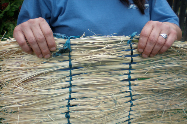 Photo of a woman holding strips of beargrass