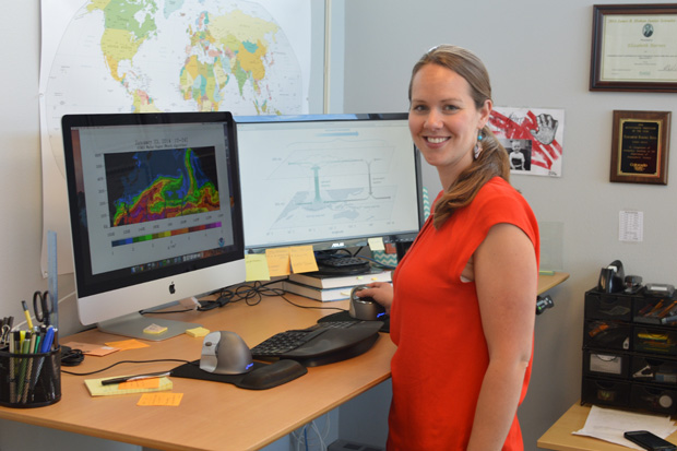 photo of libby barnes standing at her desk, with two computer monitors showing weather maps and drawings