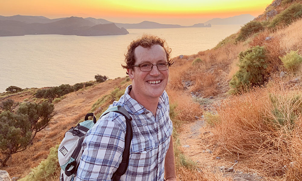 man standing on hiking trail in California with the Pacific ocean and setting sun in background