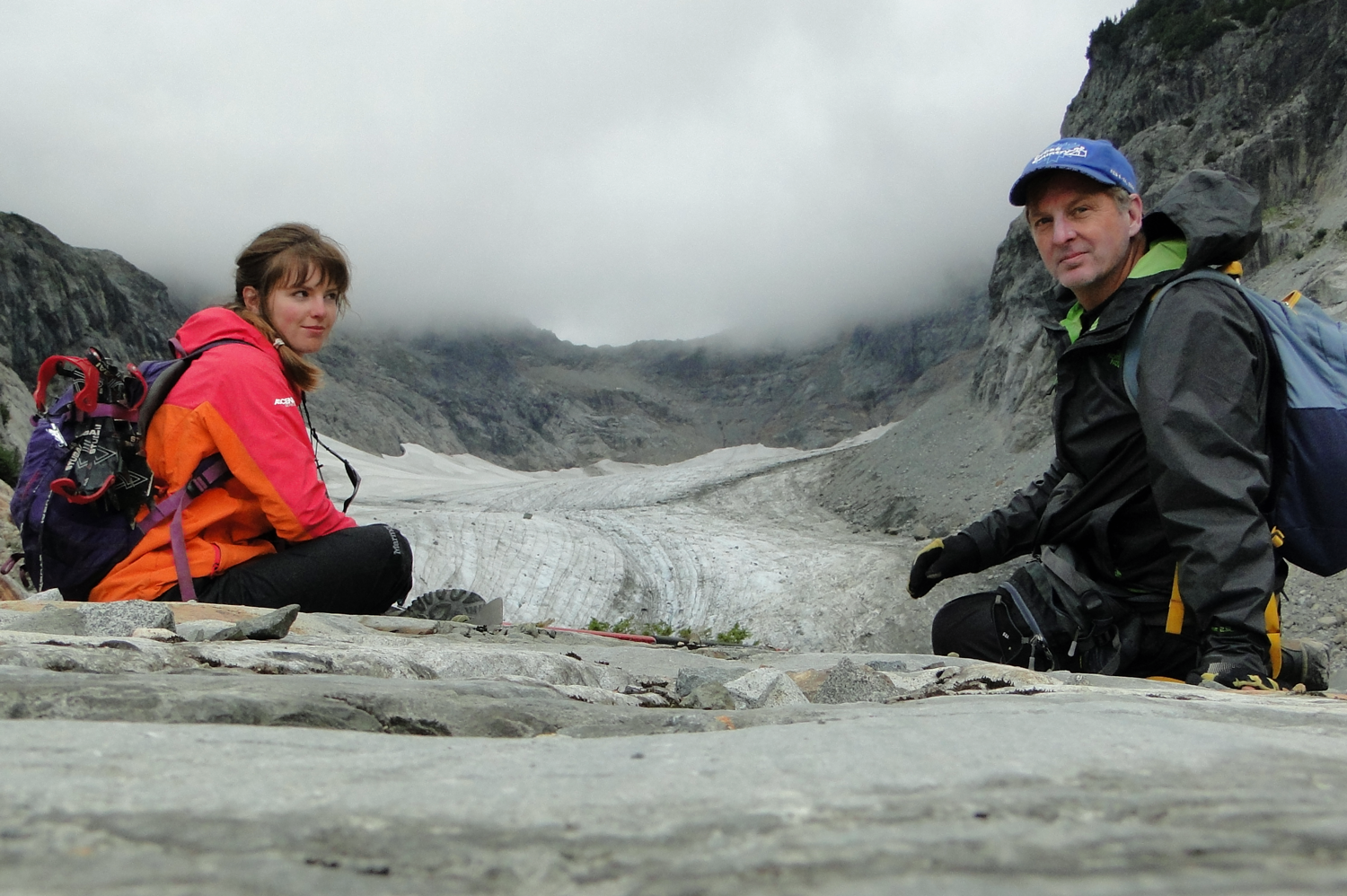 photo of Jill and Mauri Pelto sitting on a glacier wearing backpacks