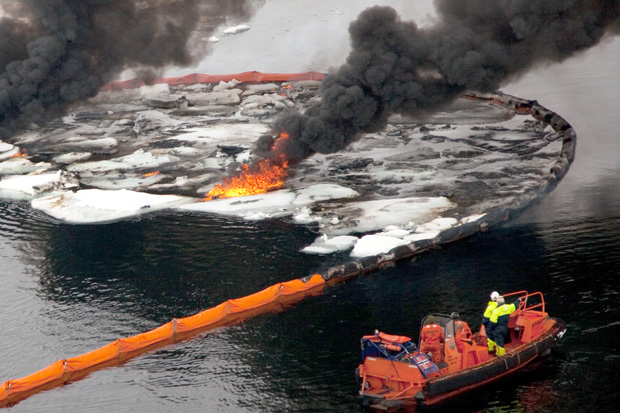 smoke billows from a burning oil slick contained with sea ice ice by a boom