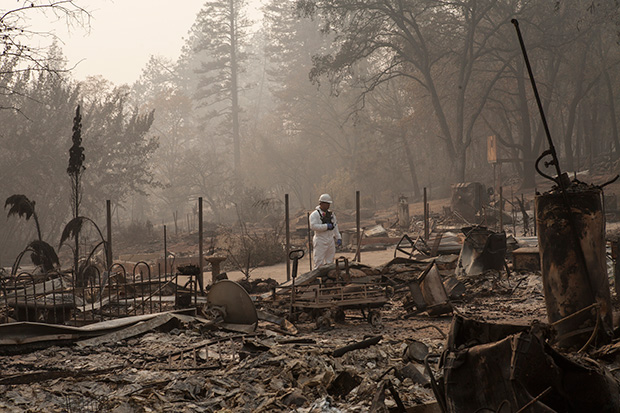 Photo of a man in a white protective suit standing amid the burned out remains of a house.